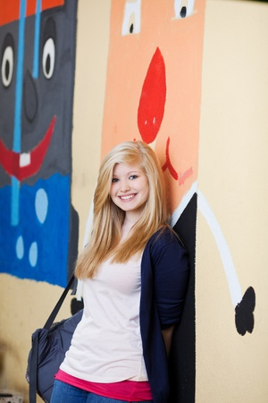Pretty young blond girl at school leaning against a brightly coloured wall painted with cartoon characters on the exterior of the school building photo