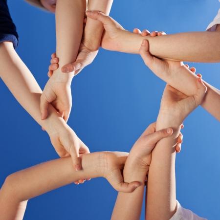 solidaridad: Amistad - una imagen conceptual de las manos de los niños pequeños agarran uno al otro en la muñeca, para formar un círculo continuo contra un cielo azul claro Foto de archivo