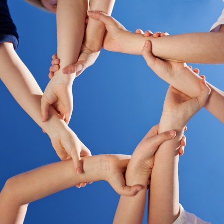 diverse hands: Friendship - a conceptual image of the hands of young children gripping each other at the wrist to form a continuous circle against a clear blue sky Stock Photo