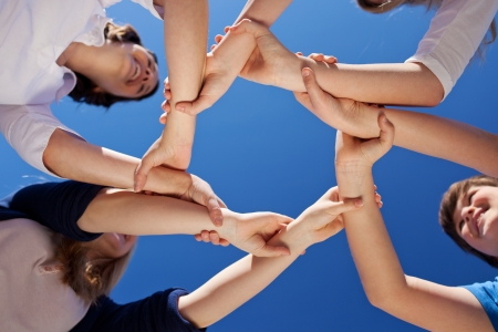 boy and girl holding hands: Low angle view of children and teacher forming frame while holding hands against clear blue sky