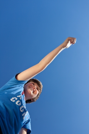 preadolescent: Low angle view of happy preadolescent boy with arms raised celebrating victory standing against blue sky