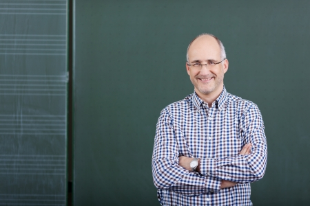 Portrait of confident male professor with arms crossed standing against chalkboard in classroom photo