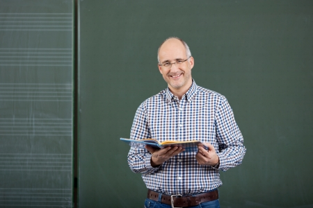 male teacher: Friendly male teacher teaching form a set of class notes standing in front of a blank green blackboard with copyspace Stock Photo