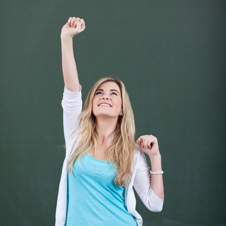 Happy teenage girl with arm raised celebrating victory against chalkboard photo