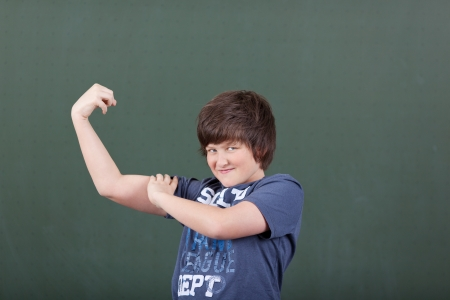 Cute young boy showing off his biceps flexing his arm in front of the blackboard in the classroom at school photo