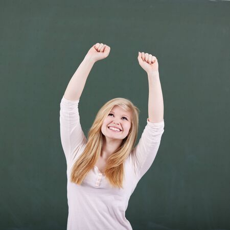 Happy teenage girl with arms raised celebrating victory against greenboard photo