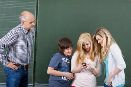 Angry teacher looking at students using mobilephone against chalkboard in classroom photo