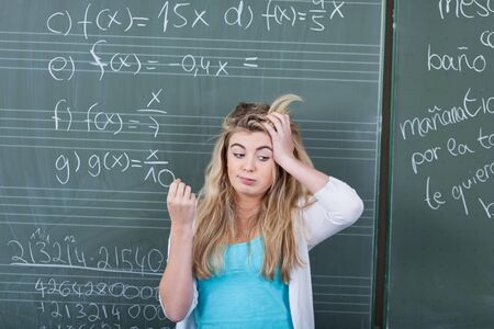 Confused teenage girl with hand on head standing against blackboard in classroom photo
