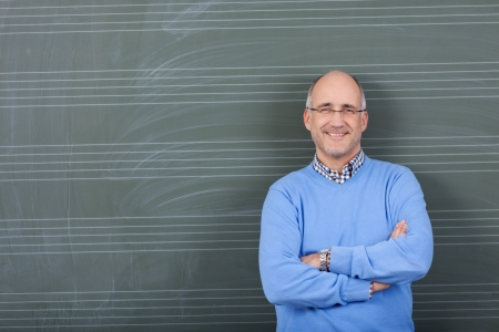 Portrait of confident male professor with hands folded standing against chalkboard in classroom