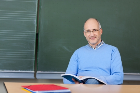 Attractive middle-aged male teacher wearing glasses preparing a lesson sitting at his desk in front of the blackboard with a textbook and notes photo