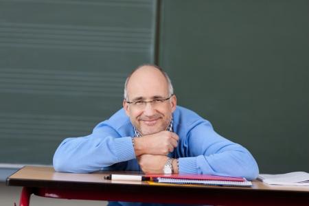 profesor: Amistoso profesor de sexo masculino se relaja en el salón de clases frente a la pizarra con la barbilla apoyada en las manos sobre el escritorio