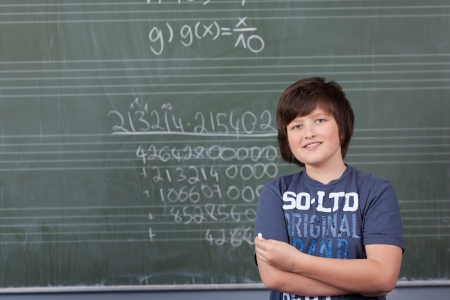 Young boy solving a maths problem in class standing with a piece of chalk in his hand in front of the blackboard covered in numbers photo