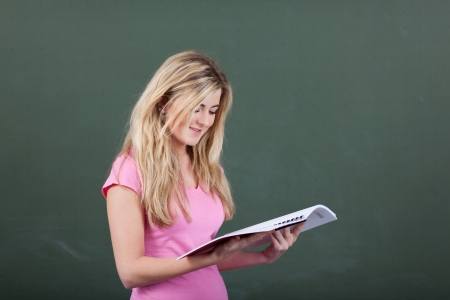 Pretty young female student reading a passage from a textbook standing in front of the blackboard Stock Photo