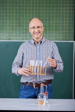 tutor: Profesor de ciencias realizaci�n de un experimento de la clase sonriendo mientras est� de pie delante de la pizarra que sostiene un bastidor de tubos de ensayo