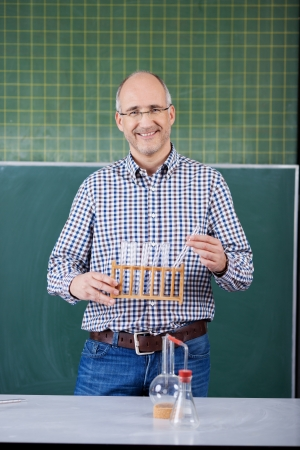 Science teacher conducting an experiment for the class smiling as he stands in front of the blackboard holding a rack of test tubes