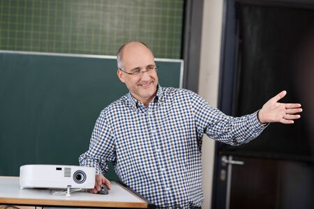 recitation: Professor at a university giving a presentation standing in front of the chalkboard with a projector gesturing with his hand for the class to look at something