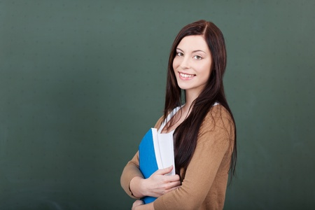 Beautiful happy young female student standing with a large binder in her arms in front of a blank chalkboard photo