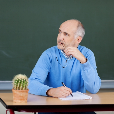 preoccupied: Male teacher sitting thinking at his desk holding his glasses in his hand and staring off to the side in contemplation