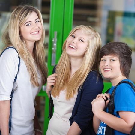 niños platicando: Tres alegres jóvenes adolescentes estudiantes de pie al aire libre en el chat durante un descanso en sus clases, dos chicas rubias y un niño