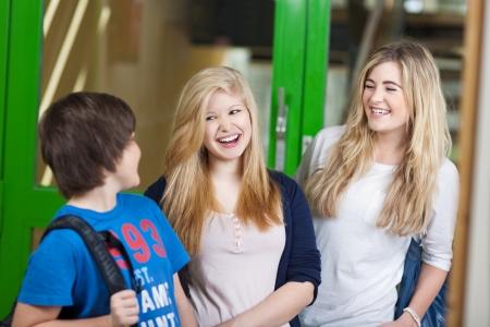 niños platicando: Tres jóvenes estudiantes riendo divertirse pie al aire libre junto relajante y charlando después de clases Foto de archivo