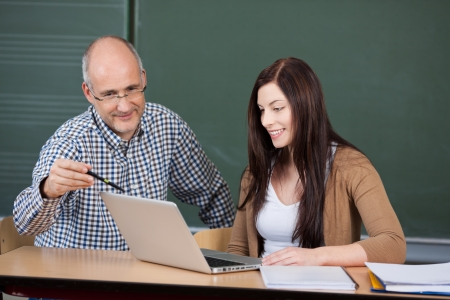 teacher training: Male professor assisting young woman in using laptop against chalkboard in classroom Stock Photo