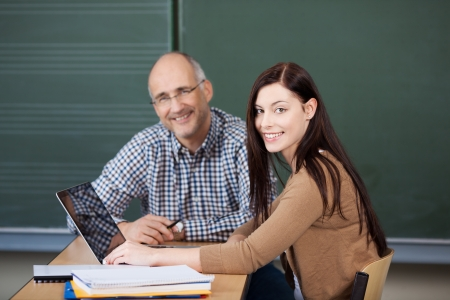Pretty young female student and middle-aged male university or college lecturer working on a laptop together Stock Photo