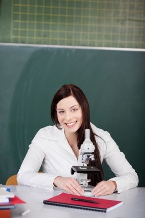 Portrait of happy young female student with microscope at desk in classroom photo
