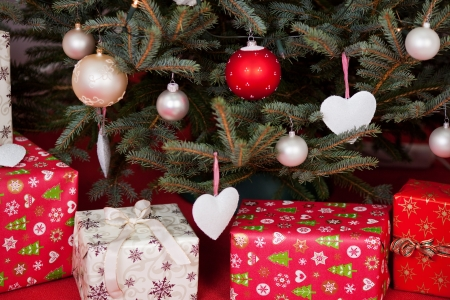 under tree: Gift boxes wrapped in decorative paper under the Christmas tree, with ornamental globes and heart shapes hanging