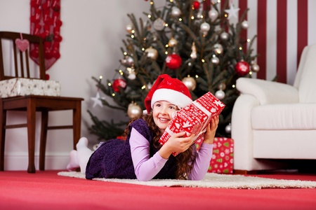unopened: Small girl hugging her unopened giftwrapped Christmas present to her cheek while lying on the carpet in front of a decorated Christmas tree in the living room Stock Photo