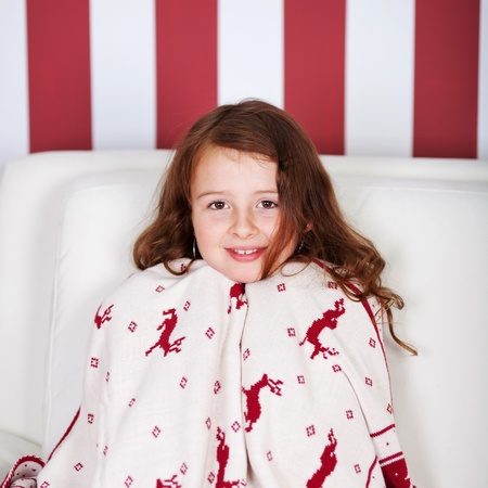 draped: Pretty little girl wrapped in Christmas cloth with galloping red reindeer sitting on a sofa looking at the camera