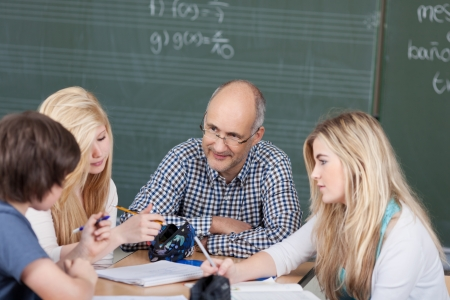 assignment: Teacher and his students in a group discussion seated around a table in the classroom discussing their notes and assignment project