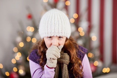 unhealthy living: Young girl with a Christmas cold and flu standing in front of the Christmas tree in a warm knitted cap, scarf and gloves coughing