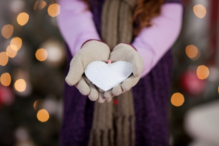 Child with a white Christmas heart displayed in cupped gloved hands surrounded by a bokeh of twinkling festive lights on a Christmas tree photo
