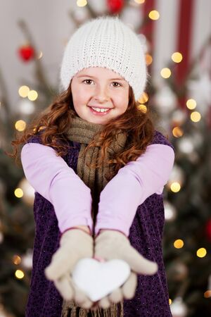 Young girl in her winter woollies standing in front of a decorated tree with a white Christmas heart displayed in her hands photo
