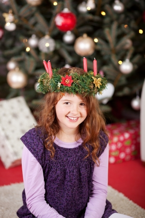 Smiling young girl sitting on the carpet in front of a decorated Christmas tree wearing a candle wreath on her head and looking up at the camera with a playful smile photo
