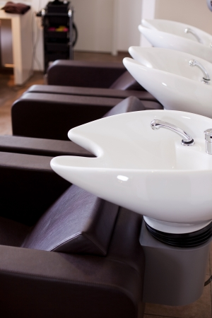 shampooing: Row of professional curved washbasins with indents for a persons neck in a hair salon with empty comfortable chairs in front of them