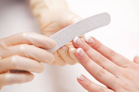 shaping: Gloved hands of a beautician filing a clients fingernails in a beauty salon during a manicure