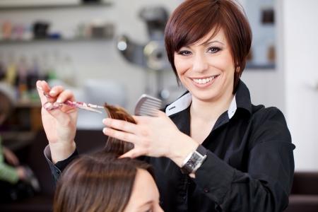 Stylist: Amistoso estilista atractivo, con corte de pelo de una mujer en una peluquería profesional una hermosa sonrisa radiante
