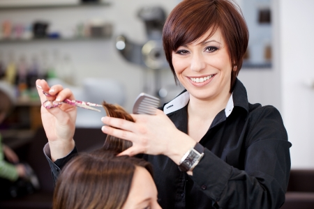 Friendly attractive hairstylist with a beautiful beaming smile cutting a womans hair in a professional hair salon