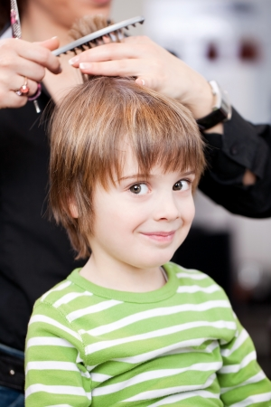 snipping: Adorable little boy getting a hair cut by a professional stylist at a hairdressing salon giving the camera a sideways look and smiling