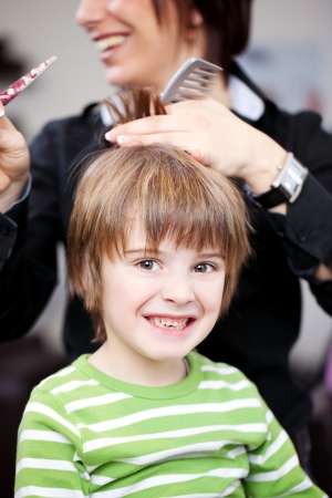 Young child in a hairdressing salon having a hair cut from a professional stylist giving the camera a beautiful smile photo