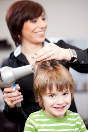 Small child having a blow dry at a hairdresser smiling at the camera with a beautiful smile photo