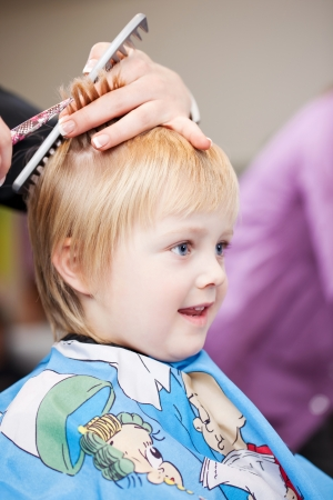 snipping: Cute little blond child getting a haircut from a professional stylist sitting in a protective cape covered in cartoon characters Stock Photo