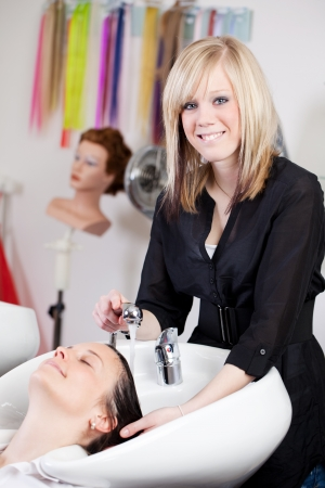 Hairdresser washing a female clients hair in the salon in a washbasin looking at the camera with a friendly smile photo