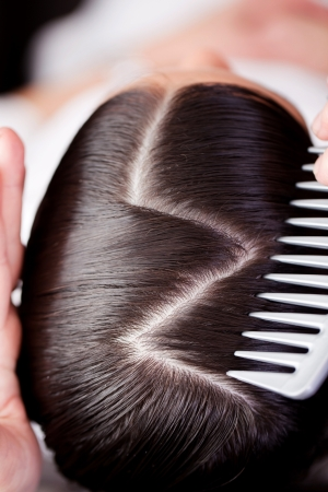 zag: Overhead view of the top of a brunette woman showing a new creative hairstyle with a zig zag path with a portion of the hairdressers comb in view