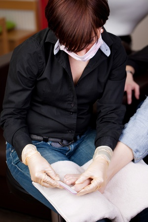 Pedicurist at work in a salon performing a pedicure on the feet of a client while wearing a mask Stock Photo - 21258772