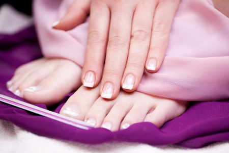 naildesign: Woman displaying her glamorous manicured finger and toe nails after a manicure in a beauty salon, close up view
