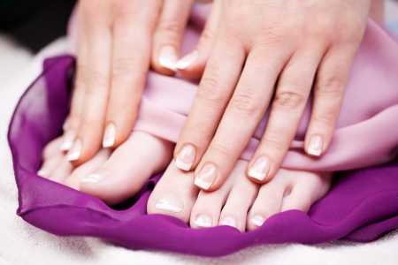 french pedicure: Woman with French manicured finger and toe nails displaying them for the viewer after enjoying a relaxing manicure in a beauty salon