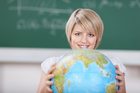 Young female student with a world globe held in her hands in front of her during a geography class at school or college photo