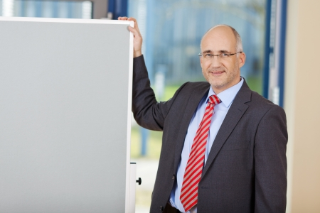 Portrait of confident mature businessman standing by flipchart in office photo